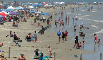 In this May 23, 2020, file photo people gather on the beach for the Memorial Day weekend in Port Aransas, Texas, Saturday, May 23, 2020