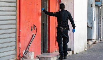 A Police officers knocks on a door of a brothel in south Tel Aviv as part of a police operation to close down bordellos in the city, March 2020.