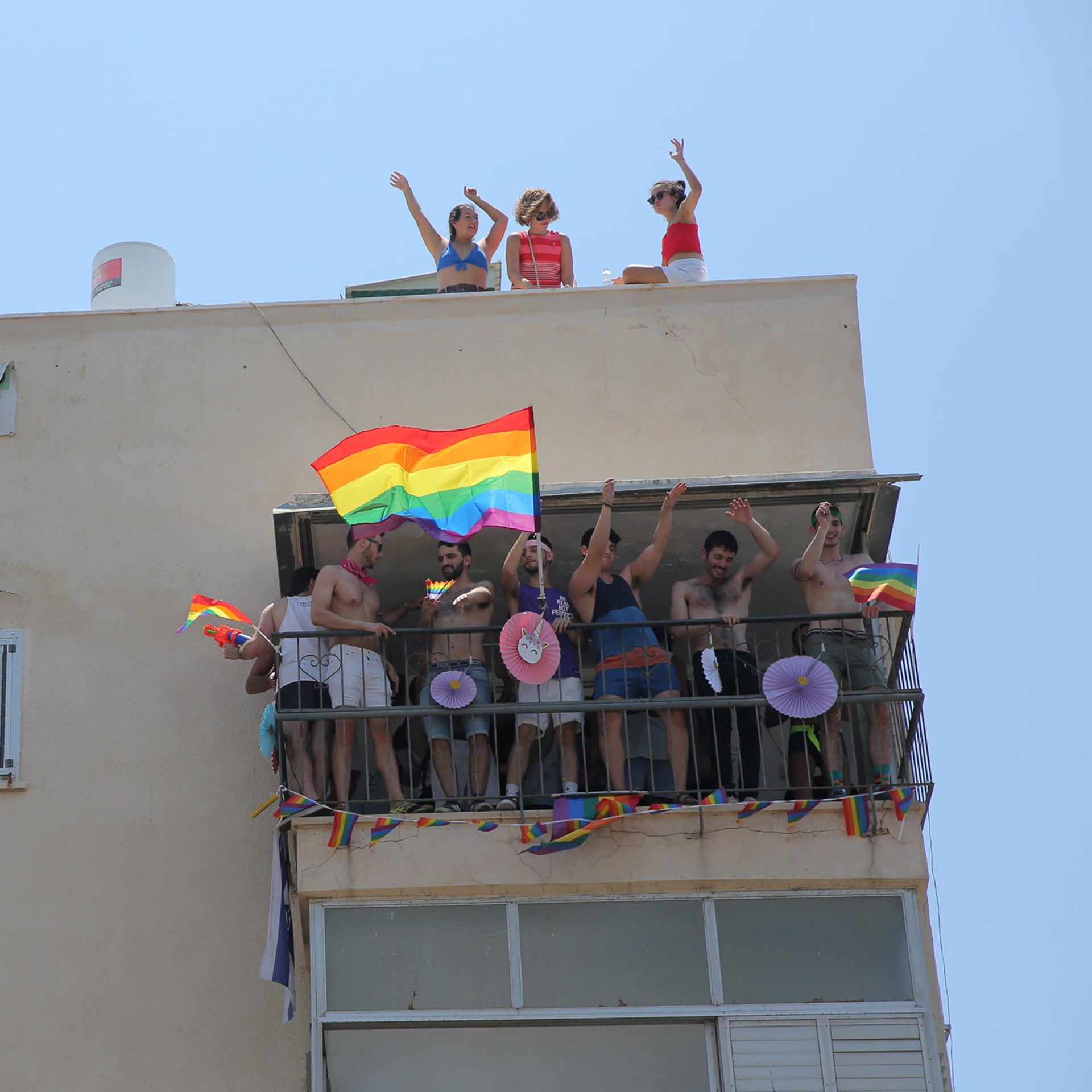 Revellers stand on a balcony during the gaya parade in Tel Aviv, 2019.