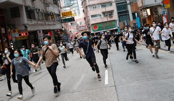 Anti-government protesters run after riot police disperse them during a march against Beijing's plans to impose national security legislation in Hong Kong, May 24, 2020.