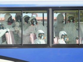 Members of the media, wearing protective suits and masks, look out from bus windows on a tour of the  crippled Fukushima Daiichi nuclear power plant in Fukushima prefecture, November 12, 2011.