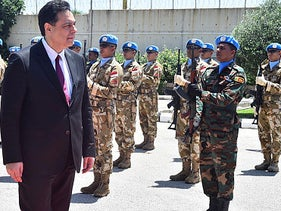 Lebanese Prime Minister Hassan Diab reviews the honor guard of the UN peacekeepers at their headquarters in the southern coastal border town of Naqoura, Lebanon, on Wednesday, May 27, 2020.