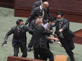 Pro-democracy lawmaker Ted Hui struggles with security personnel at the main chamber of the Legislative Council during the second day of debate on a bill that would criminalize insulting or abusing the Chinese anthem in Hong Kong, May 28, 2020.
