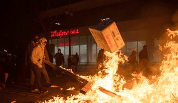A protester pulls a burning board from a fire set in response to the death of George Floyd in downtown Oakland, California, May 29, 2020.