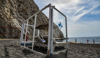 Plexiglass panels protect an umbrella and sunbeds as a preventive measure taken to curb the spread of the COVID-19 pandemic on the Greek Aegean island of Santorini, May 20, 2020.
