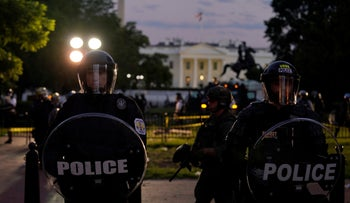 Uniformed Secret Service officers in riot gear stand in front of the White House as demonstrators gather to protest the death of George Floyd, Washington, May 30, 2020.