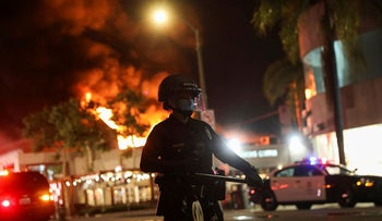 A law enforcement officer takes position as a building burns during nationwide unrest following the death in Minneapolis police custody of George Floyd, in Los Angeles, California, U.S., May 30, 2020