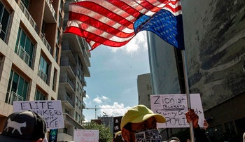 A protester holds up an upside down US flag during a protest against police brutality in Miami, Florida on May 30, 2020