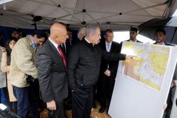 Israeli Prime Minister Benjamin Netanyahu checks a map of the area during a visit to the Ariel settlement in the West Bank. Feb. 24, 2020