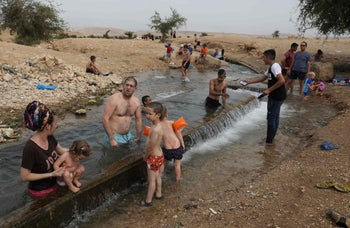 Palestinian youths and Jewish settlers gather at a water spot near the West Bank village of al-Auja in the Jordan valley, May 15, 2020.