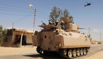 Egyptian Army soldiers patrol in an armored vehicle backed by a helicopter gunship during a sweep through villages in in Sheikh Zuweid, northern Sinai, Egypt, May 21, 2013.