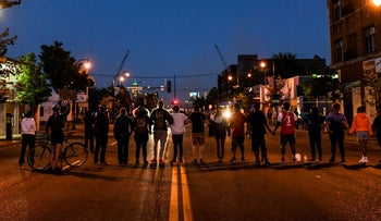 Protestors form a human chain in front of police officers during a demonstration to call for justice for George Floyd. May 30, 2020 in Minneapolis, Minnesota