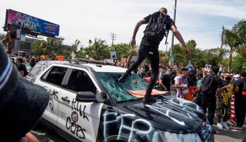 Demonstrators smashing a police vehicle in the Fairfax District as they protest the death of George Floyd, Los Angeles, California, May 30, 2020.