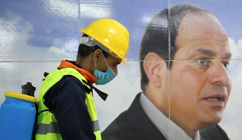 A member of a medical team sprays disinfectant as he passes an image of President Sissi, Cairo, March 22, 2020.