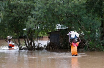 Residents carry their belongings inside flood water as they evacuate from their home after River Nzoia burst its banks and due to the backflow from Lake Victoria, in Nyadorera, Siaya County, Kenya May 2, 2020