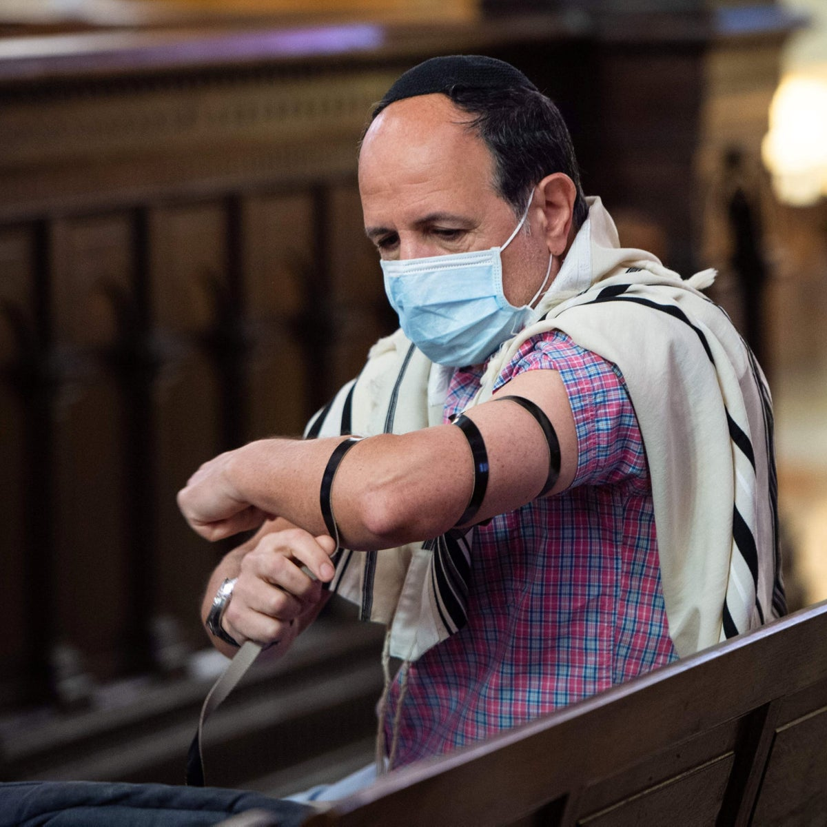An illustrative photograph of a Jewish man wearing a protective face mask and laying tefillin on his arm, at the Great Synagogue of Marseille, May 28, 2020.