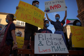 Protesters hold signs during a demonstration against the Israeli police after they shot and killed Palestinian man Eyad Hallaq, Jaffa, May 31, 2020