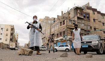 Security men wearing protective masks stand on a street during a 24-hour curfew amid concerns about the spread of the coronavirus disease (COVID-19), in Sanaa, Yemen. May 6, 2020.