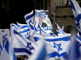 Supporters of Benjamin Netanyahu wave Israeli flags during a rally as his corruption trial opens, near the Jerusalem District Court, May 24, 2020.