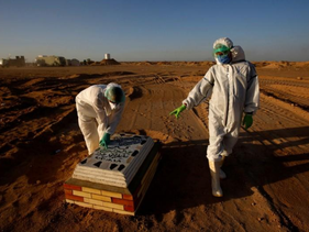 Abdelhussan Kadhim checks a name on a grave of a Christian man who passed away due to coronavirus at the new Wadi Al-Salam cemetery on the outskirts of the holy city of Najaf, Iraq, May 25, 2020.