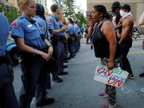 A weeping protester confronts police during nationwide unrest following the death of George Floyd, Raleigh, North Carolina, May 30, 2020.