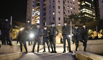 Police officers stand guard during a protest against police violence in Tel Aviv, May 31,2020.