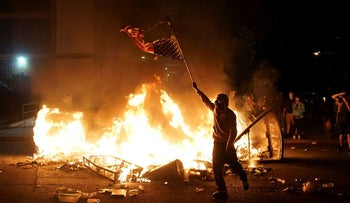 A protestor waves a burned American flag over a fire during a protest against the death in Minneapolis police custody of African-American man George Floyd, in St Louis, Missouri, U.S., June 1, 2020