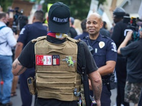A member of the far-right Boogaloo Bois militia walking next to protesters demonstrating outside a police department just outside of downtown Charlotte, North Carolina, May 29, 2020.