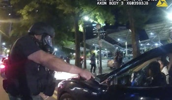 An officer points his handgun at Messiah Young while the college student is seated in his vehicle, in Atlanta, May 30, 2020.