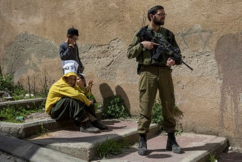 Settler kids behind an Israeli soldiers in the contested West Bank city of Hebron, on March 10, 2020.