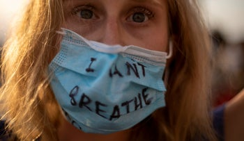 A protester wears a face mask during a protest to decry the killing of George Floyd in front of the American embassy's Tel Aviv branch, June 2, 2020
