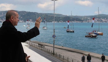 Turkish President Recep Tayyip Erdogan salutes vessels in the Bosporus Strait in Istanbul, May 29, 2020.