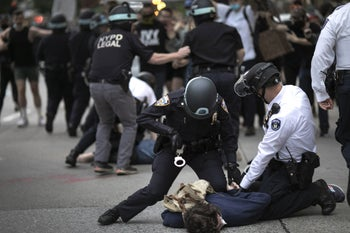 Police arresting a protester refusing to get off the streets during an imposed curfew in New York while marching in a solidarity rally calling for justice over the death of George Floyd, June 2, 2020.