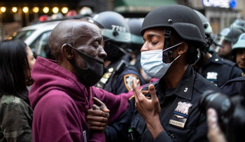 A protester and a police officer shake hands in the middle of a standoff during a solidarity rally calling for justice over the death of George Floyd, New York, June 2, 2020.