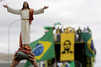 A supporter of Brazil's President Jair Bolsonaro holds up a statue of Jesus Christ during a protest against former Justice Minister Sergio Moro and the Supreme Court, in front of the National Congress in Brasilia. May 9, 2020