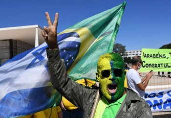 A supporter of Jair Bolsonaro backed by a hybrid Brazilian-Israeli flag at a demonstration of support for Brazil's president support. Brasilia, May 31, 2020
