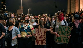Protesters denouncing police brutality and systemic racism are kept in place on the Manhattan Bridge by police for hours during a citywide curfew in New York City.