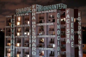 "The slogan: ""Out Bolsonaro"" and the words ""Coward, Facist, Ignorant, Genocidal, Worm, Criminal"" projected on a Sao Paulo building to protest President Jair Bolsonaro's coronavirus failures. Brazil, March 26, 2020"