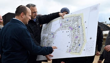 A January 21, 2020 photo shows then Defense Minister Naftali Bennett being shown construction plans in the West Bank.