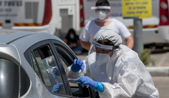 Students and staff from the Jerusalem's Gymnasia high school get tested in the parking of Teddy Stadium in Jerusalem, June 2020.
