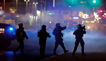 In this May 30, 2020, file photo, police walk through tear gas as they try to disperse protesters in Las Vegas