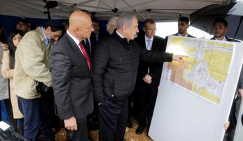 Prime Minister Benjamin Netanyahu checks the area map during visit to Ariel settlement in the West Bank, February 24, 2020