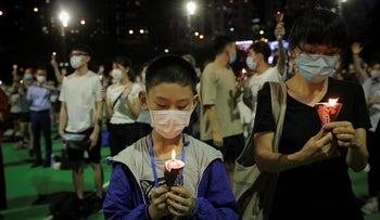 Participants holds candles during a vigil for the victims of the 1989 Tiananmen Square Massacre at Victoria Park in Causeway Bay, Hong Kong, June 4, 2020.