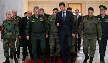 Syrian President Bashar Assad speaks with Russian Defense Minister Sergei Shoigu before their meeting in Damascus, Syria, March 23, 2020.