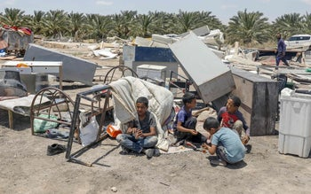 Bedouin boys sit near the rubble of a tent in the Deir Hajle Bedouin community, east of the Palestinian city of Jericho, June 3, 2020.