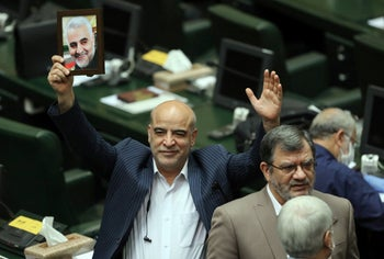 A MP holds up a portrait of slain Iranian General Qassem Soleimani during the inaugural session of the new parliament in Tehran, May 27, 2020.