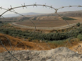 A portion of the Israeli-Jordanian border is viewed through a barbed wire fence from Baqoura, in the Jordan Valley, November 13, 2019.