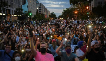 Protesters hold up their phones during a demonstration over the death of George Floyd, outside the White House on June 3, 2020 in Washington, DC.