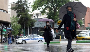 Iranians wear protective face masks, following the outbreak of the coronavirus disease (COVID-19), as they walk in Vali-E-Asr street, in Tehran, Iran, May 20, 2020.