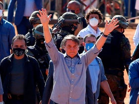 Brazilian President Jair Bolsonaro (C) waves to supporters during the inauguration of a field hospital in Aguas Lindas, in the State of Goiais, Brazil, June 5, 2020.